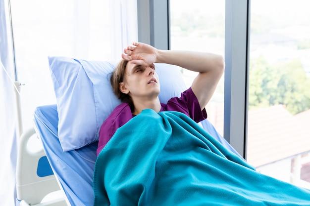 Un patient a des maux de tête et fait de la fièvre avec un visage anxieux allongé sur le lit à l'hôpital de la chambre.