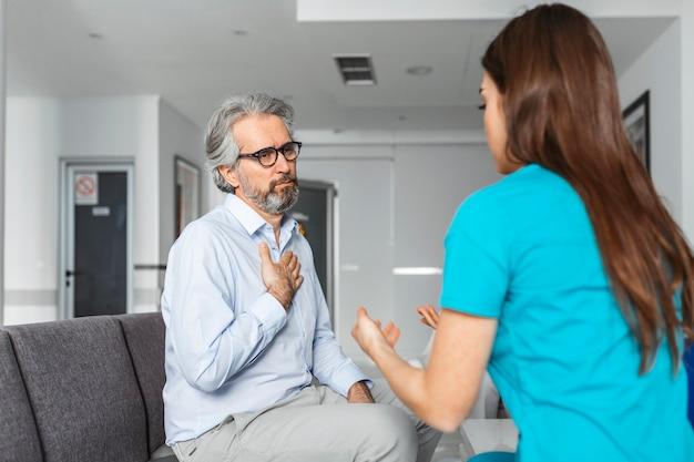 Patient avec médecin dans la salle d'attente de l'hôpital discutant de ses symptômes.