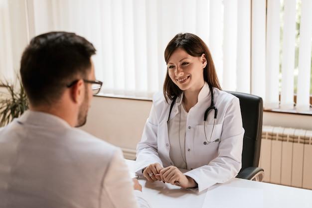 Patient parlant à une jeune femme médecin dans un hôpital.