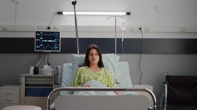 Patient portant avec tube à oxygène nasal regardant dans la caméra assis dans son lit
