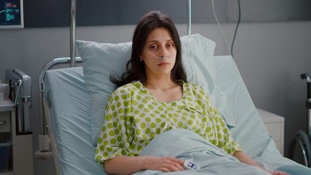 Patient portant avec un tube à oxygène nasal regardant dans la caméra