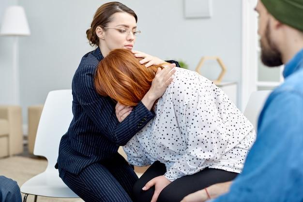 Patient réconfortant pendant une séance de thérapie de groupe