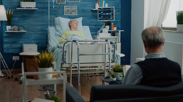 Patient à la retraite atteint d'une maladie assis dans un lit d'hôpital