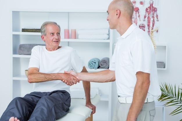 Patient se serrant la main avec un médecin
