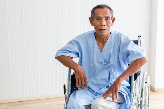 Patient senior dans son fauteuil roulant à l'hôpital.