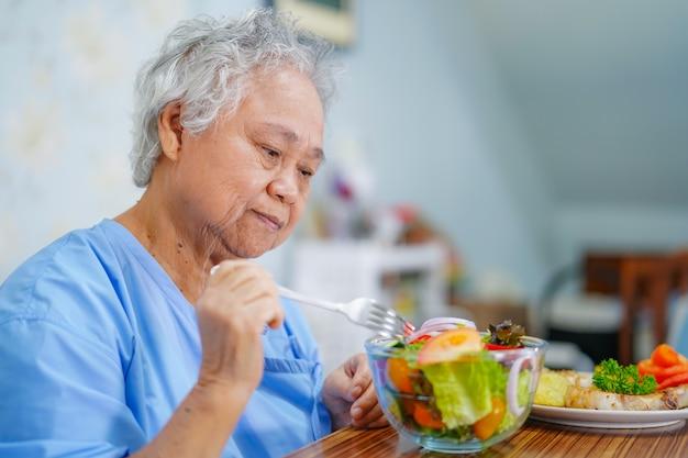 Patient senior femme asiatique manger le petit déjeuner à l'hôpital.