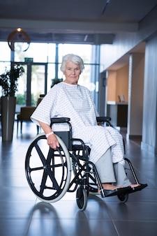 Patient senior handicapé en fauteuil roulant dans le couloir de l'hôpital