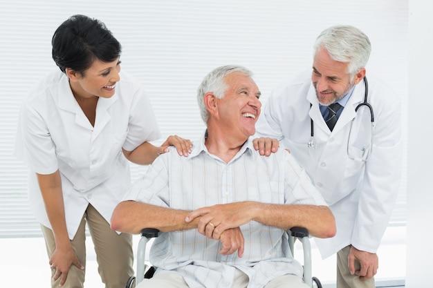 Patient senior heureux avec des médecins assis dans un fauteuil roulant