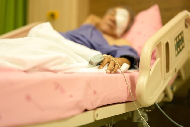 Patient senior avec jauge de pouls pour mesurer le rythme cardiaque sur un doigt âgé du patient.