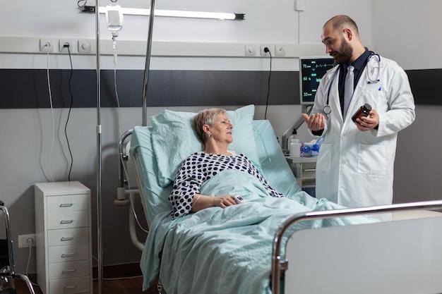 Patient senior malade portant dans son lit d'hôpital
