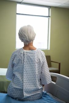 Patient senior réfléchi assis à l'hôpital
