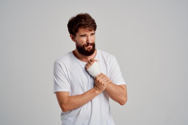 Patient de sexe masculin dans un t-shirt blanc avec une main bandée posant sur fond clair