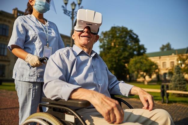 Patient de sexe masculin avec des lunettes de réalité virtuelle assis dans un fauteuil roulant