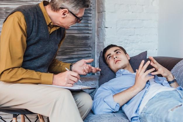 Patient de sexe masculin malheureux écoutant les conseils d'un conseiller psychologue. homme regardant désespérément psychologue senior.