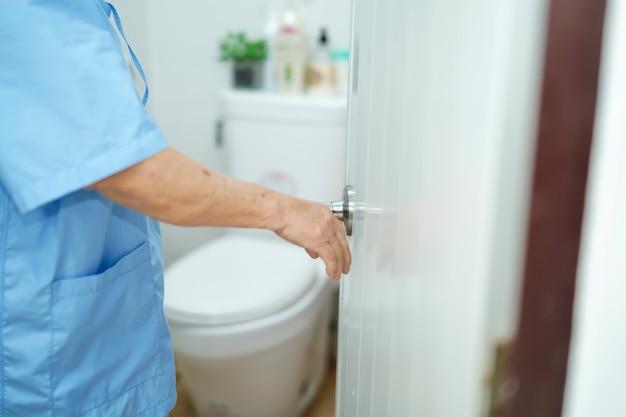 Patiente âgée âgée âgée de femme âgée de femme asiatique ouvrez les toilettes à la main dans l'hôpital de soins infirmiers