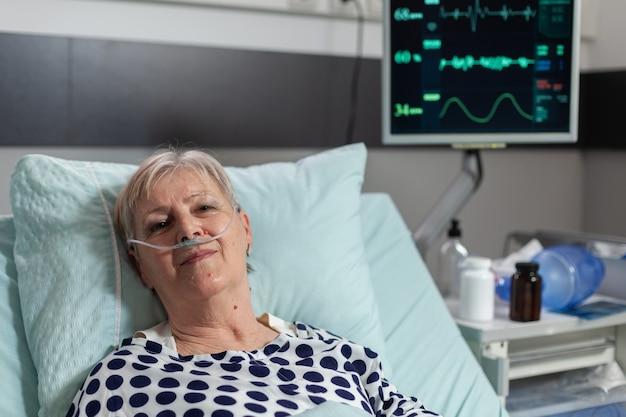 Patiente âgée allongée dans un lit d'hôpital après un traitement de récupération recevant un médicament...