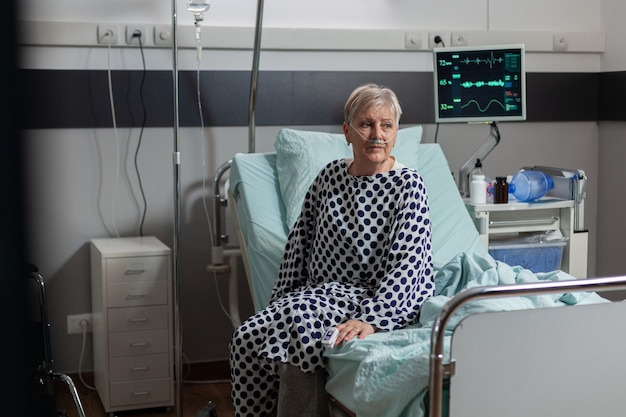 Patiente âgée assise sur le bord du lit dans un lit d'hôpital