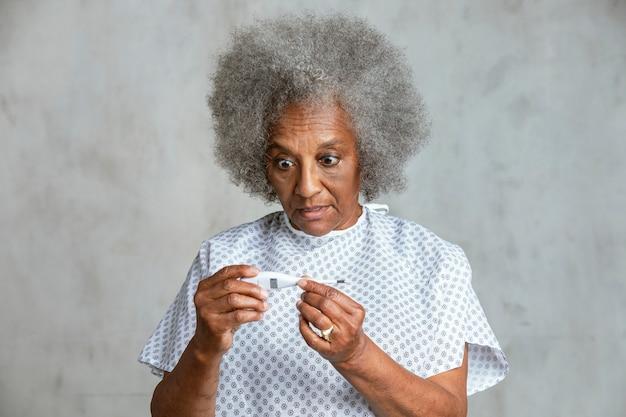 Patiente âgée choquée vérifiant sa température