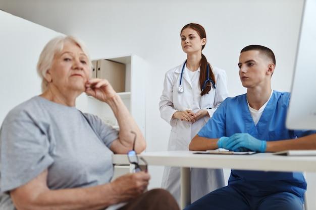 Patiente âgée dans l'assistant de service de bureau de médecins