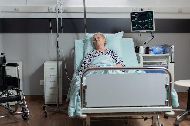 Patiente âgée portant dans son lit d'hôpital