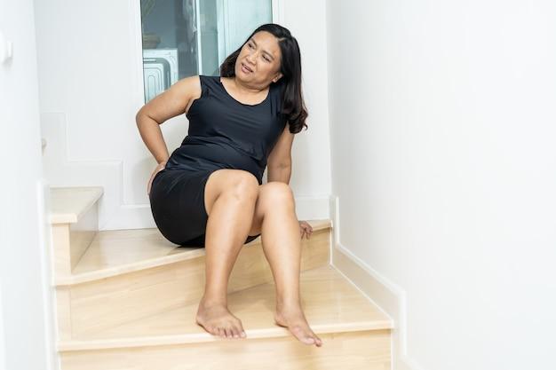 Une patiente asiatique d'âge moyen tombe dans les escaliers à cause de surfaces glissantes