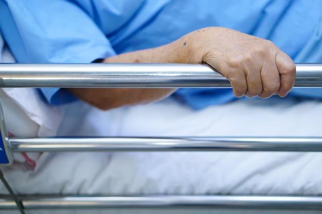 Patiente asiatique âgée ou âgée âgée allongée, manipuler le lit du rail avec espoir.