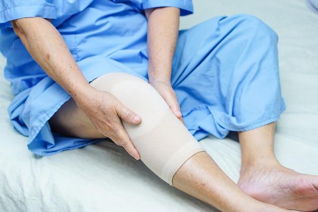 Patiente asiatique âgée ou âgée âgée avec un soutien-douleur au genou.