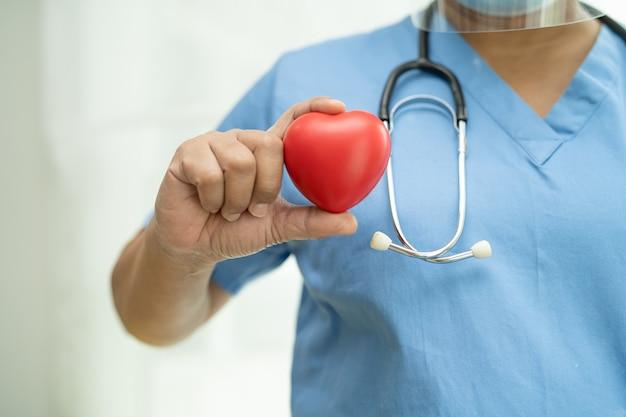 Patiente asiatique âgée ou âgée de vieille dame tenant un coeur rouge dans sa main sur le lit dans une salle d'hôpital de soins infirmiers, concept médical fort et sain