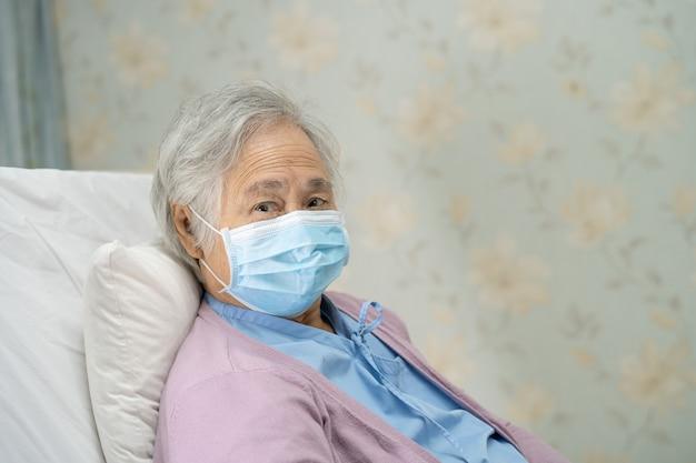 Patiente asiatique âgée portant un masque facial à l'hôpital pour protéger le coronavirus covid19
