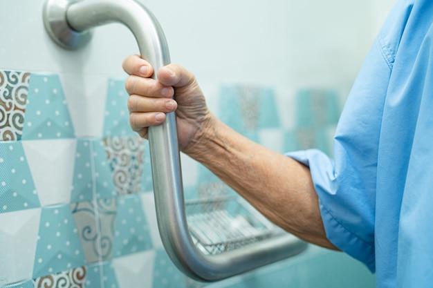 Une patiente asiatique âgée utilise la sécurité de la poignée dans un hôpital de soins infirmiers
