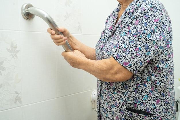 Une patiente asiatique âgée utilise la sécurité de la poignée dans les toilettes à l'hôpital