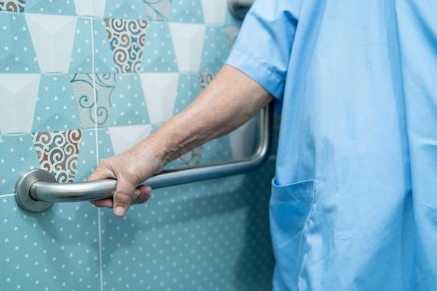 Une patiente asiatique âgée utilise la sécurité de la poignée de la salle de bain des toilettes