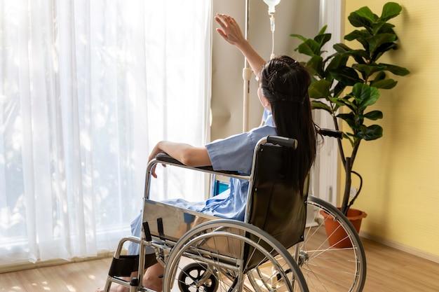 Patiente asiatique assis dans le fauteuil roulant à la chambre d'hôpital.