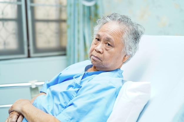Patiente asiatique assise sur un lit à l'hôpital.
