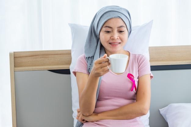 Une patiente asiatique atteinte d'un cancer du sein tenant une tasse de café avec un ruban rose portant un foulard après un traitement de chimiothérapie au lit dans la chambre à coucher à la maison, soins de santé, médecine