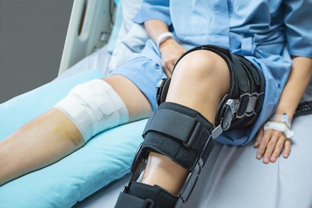 Patiente asiatique avec bandage compression genou brace soutien blessure sur le lit en soins infirmiers hospitaliers. soins de santé et soutien médical.