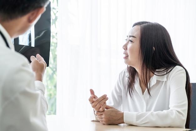 Patiente asiatique et médecin discutent