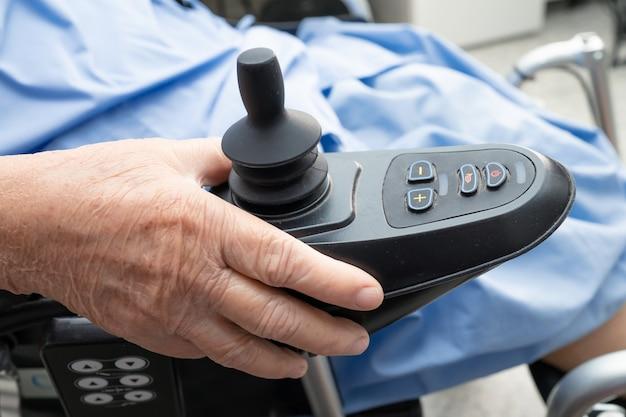 Patiente asiatique senior sur fauteuil roulant électrique avec télécommande.