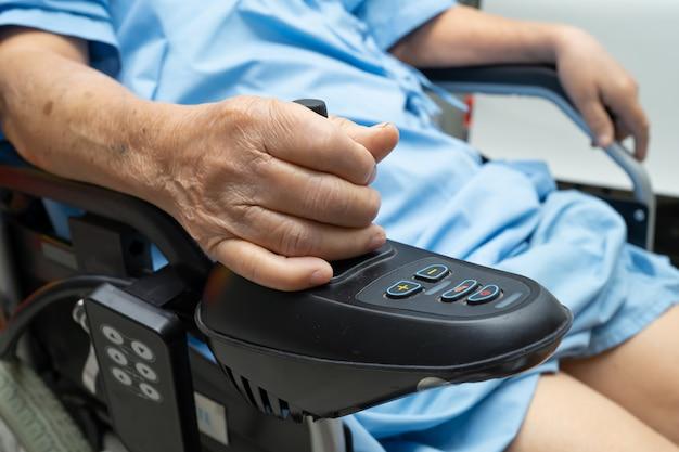 Patiente asiatique senior sur un fauteuil roulant électrique.
