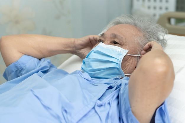 Patiente asiatique senior portant un masque facial à l'hôpital pour protéger le virus covid-19.