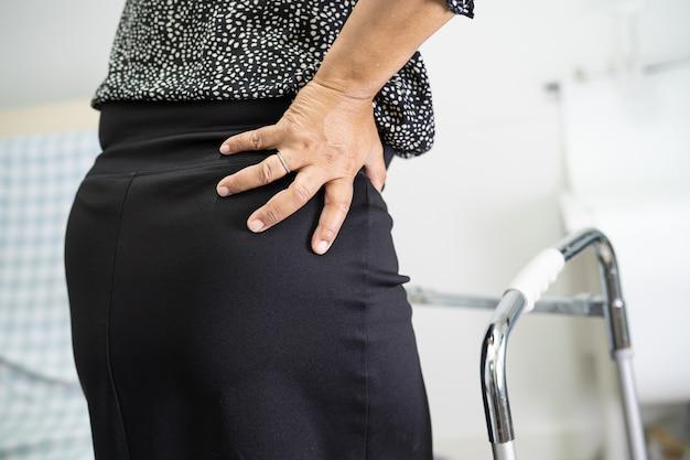 Une patiente asiatique souffre de son dos orthopédique au poignet lombaire avec marchette.