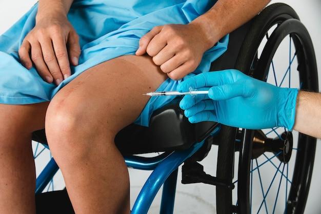 Patiente malade recevant une injection au genou par un médecin