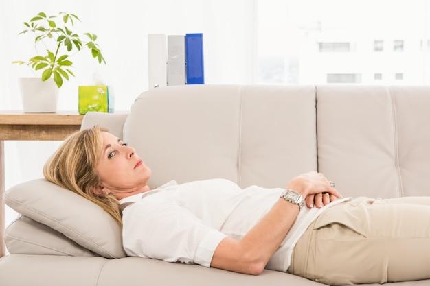 Patiente malheureuse couchée sur un canapé de thérapeutes