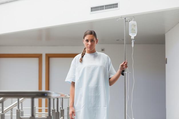 Patiente marchant avec un stand de goutte à goutte