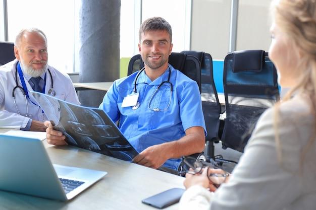 La patiente et les médecins ont une consultation dans la chambre d'hôpital.