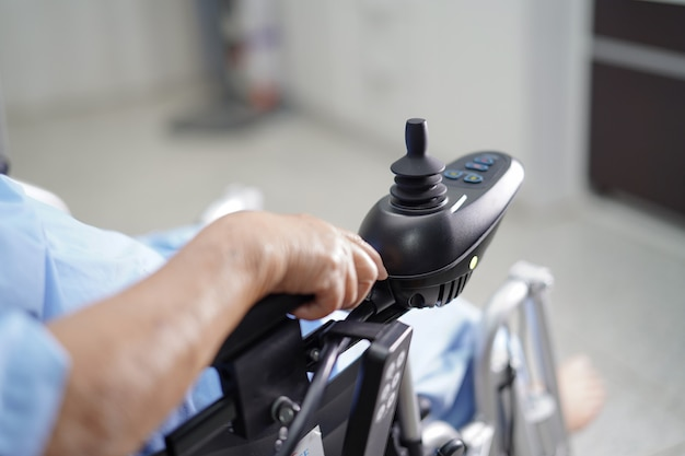 Patiente senior asiatique sur fauteuil roulant électrique.