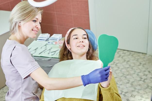 Patiente vérifiant les dents dans le miroir. jeune fille au bureau de dentiste. nouveaux implants dentaires.