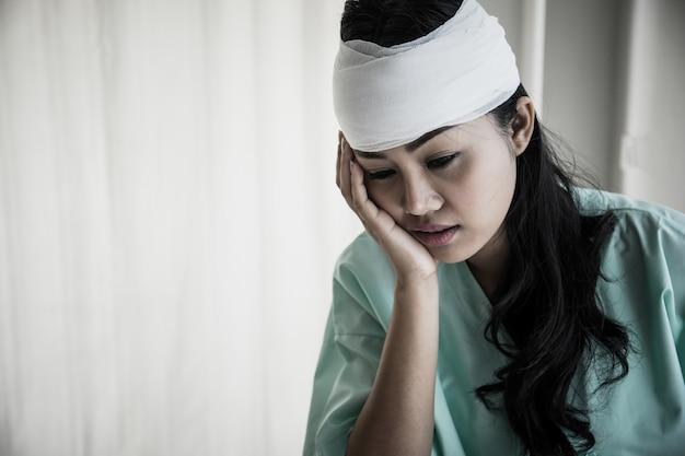 Patientes ayant des douleurs dans la tête après une hospitalisation assis sur un fauteuil roulant dans la chambre du patient