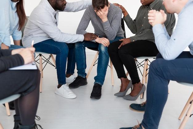 Les patients masculins consolant l'homme triste