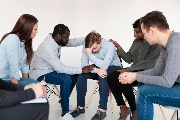 Les patients en réadaptation consolent l'homme triste